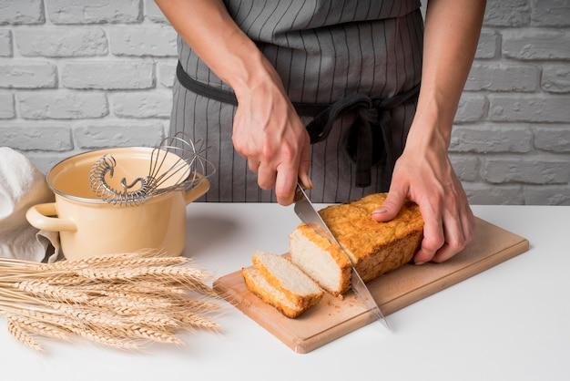 Hoge hoek vrouw snijden bananenbrood