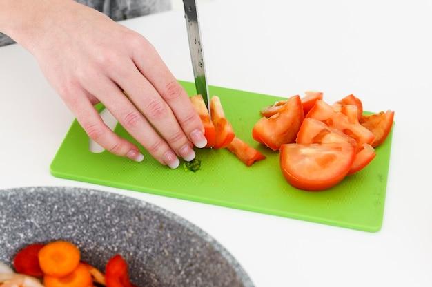 Hoge hoek vrouw snijden tomaten