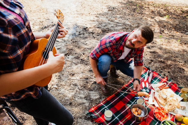 Hoge hoek vrouw spelen instrument en man koken