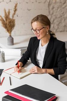 Hoge hoek vrouwelijke leraar die aantekeningen maakt