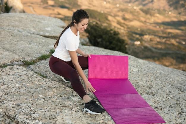 Hoge hoek vrouwelijke selectieplaats om yoga uit te oefenen