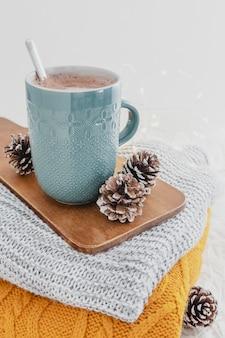Hoge hoek warme chocolademelk met dekens en dennenappels