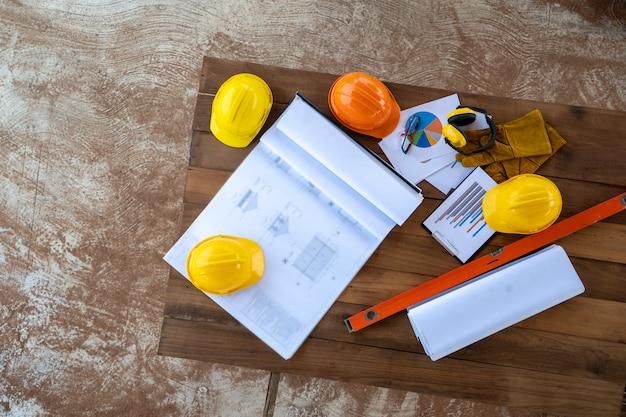Hoge hoek weergave bouwmachines, blauwdrukken en bouw tools op houten tafel