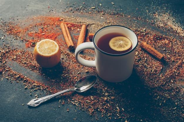 Hoge hoek weergave citroenthee en gedroogde kruiden met droge kaneel, lepel en citroen