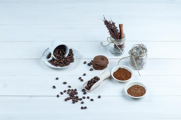 Hoge hoek weergave cookies, kopje koffiebonen met kom oploskoffie, potje kruiden op witte houten plank achtergrond. horizontaal