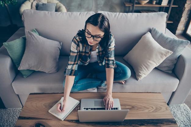 Hoge hoek weergave foto van mooie zakelijke dame sms notebook collega's thuis werken opmerken opstarten details in organisator dragen casual kleding zitten sofa binnenshuis