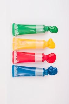 Hoge hoek weergave kleurrijke verfbuizen geperst op wit papier