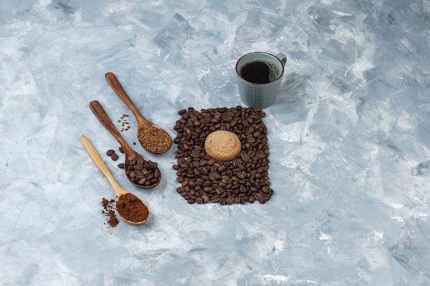 Hoge hoek weergave kopje koffie, koekje met koffiebonen, instant koffie, koffiemeel in houten lepels op lichtblauwe marmeren achtergrond. horizontaal