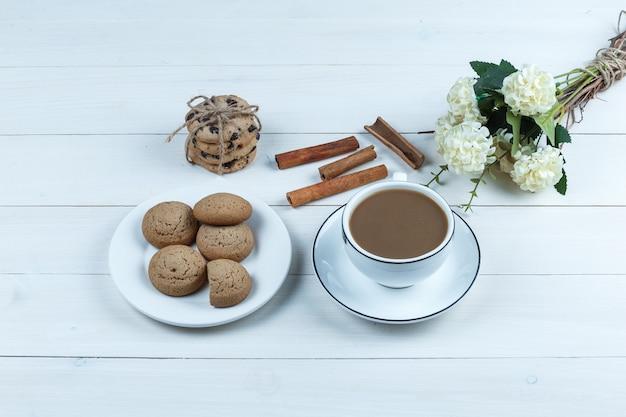 Hoge hoek weergave kopje koffie met bloemen, kaneel, verschillende soorten koekjes op witte houten plank achtergrond. horizontaal