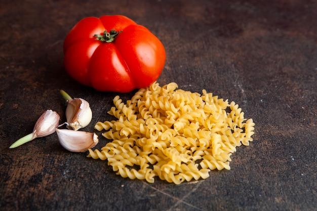 Hoge hoek weergave macaroni met tomaat en knoflook op donkere gestructureerde achtergrond. horizontaal