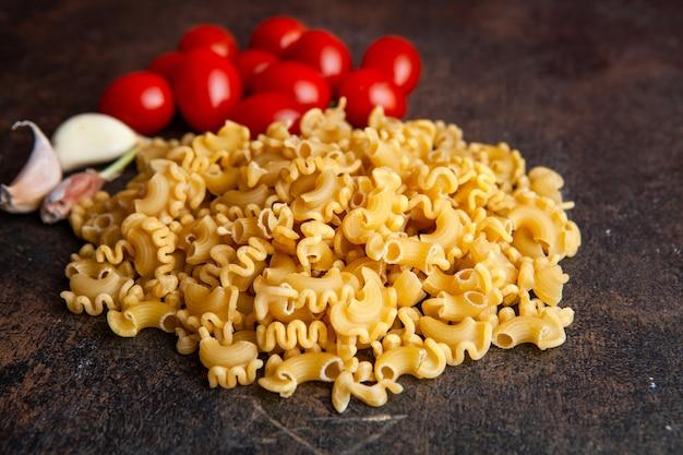 Hoge hoek weergave macaroni met tomaten en knoflook op donkere gestructureerde achtergrond. horizontaal