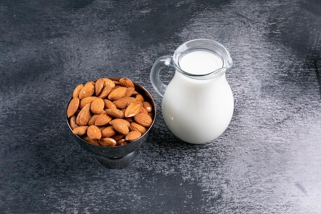Hoge hoek weergave melk en amandelen op zwarte stenen tafel.
