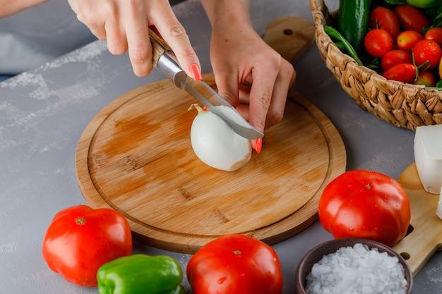 Hoge hoek weergave vrouw snijden ui in tweeën op snijplank met mes, groene paprika, komkommer, zout op grijze ondergrond