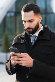 Hoge hoek zakelijke man telefoon controleren