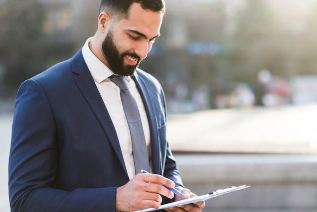 Hoge hoek zakenman controleren klembord