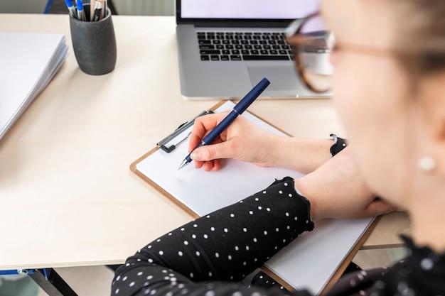 Hoge hoek zakenvrouw maken van aantekeningen