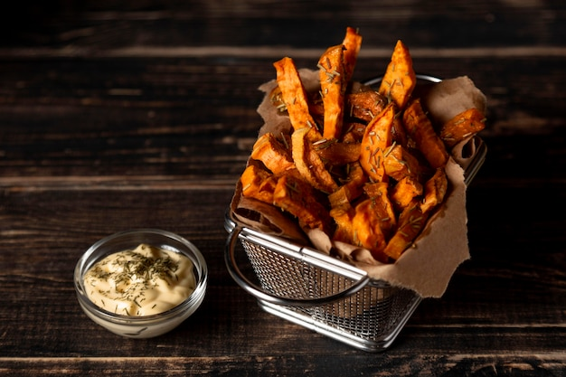Hoge hoek zoete aardappelfrietjes met saus