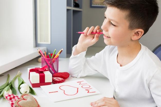 Hoge hoek zoon schrijfkaart voor zijn moeder
