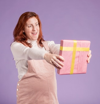 Hoge hoek zwangere vrouw die gift bekijkt