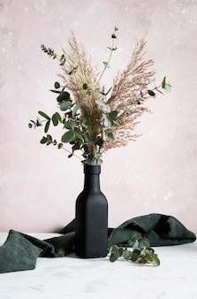 Hoge hoek zwarte vaas met bloemenboeket