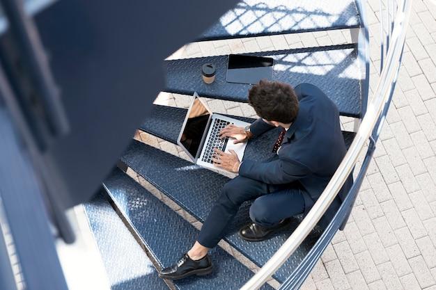 Hoge hoekadvocaat met laptop, tablet en koffie