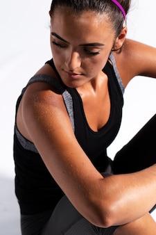 Hoge hoekatleet die in gymnastiekkostuum neer kijkt