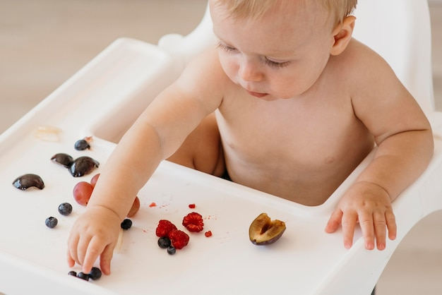 Hoge hoekbaby die in hoge stoel kiest wat te eten fruit