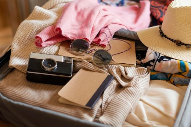 Hoge hoekbagage met kleding en camera
