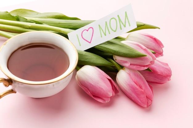 Hoge hoekbeker met thee naast tulpen