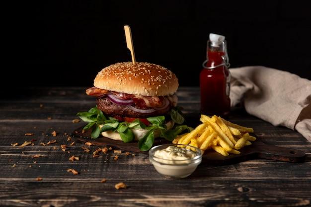 Hoge hoekburger met frietjes en sauzen op tafel