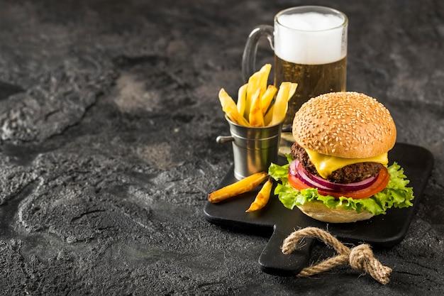 Hoge hoekburger op snijplank met frietjes, saus en bier met kopie-ruimte