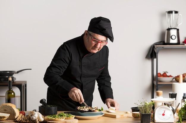Hoge hoekchef die salade voorbereidt