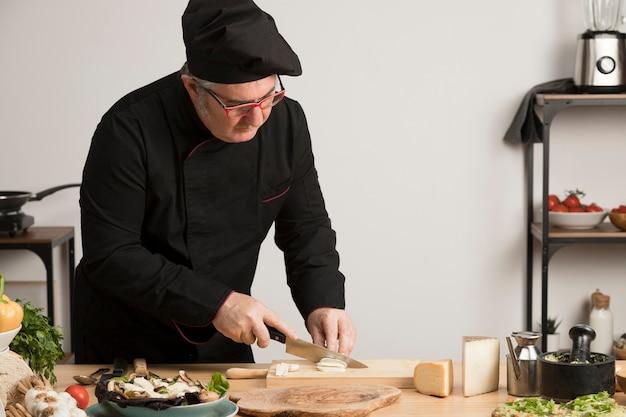 Hoge hoekchef-kok in keuken scherpe ingrediënten