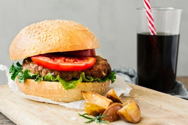 Hoge hoekclose-up van hamburger en gebraden gerechten op houten raad