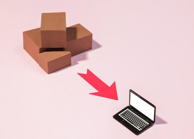 Hoge hoekdozen, rode pijl en laptop