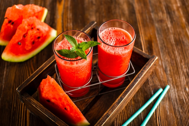 Hoge hoekglazen in bekerhouder met watermeloensap