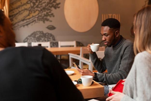 Hoge hoekgroep vrienden die koffie drinken