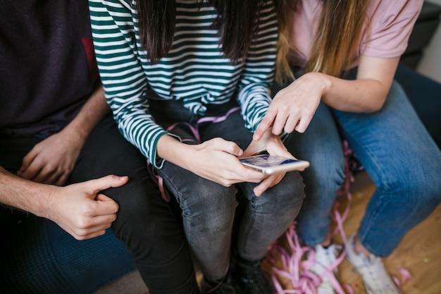 Hoge hoekgroep vrienden die telefoon controleren