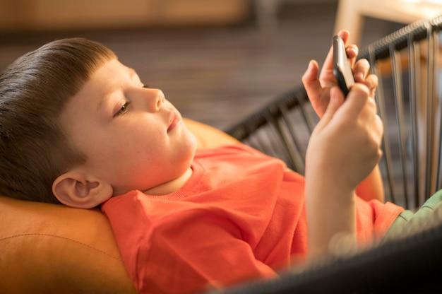 Hoge hoekjongen die thuis op mobiel speelt