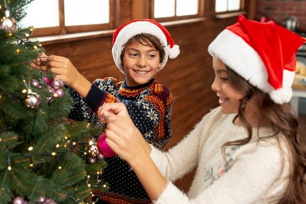 Hoge hoekkinderen die de kerstboom versieren