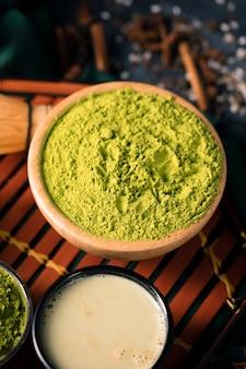 Hoge hoekkom met groen poeder voor thee