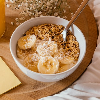 Hoge hoekkom met ontbijtgranen en banaan