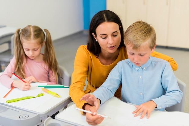 Hoge hoekleraar helpt een kleine jongen in de klas