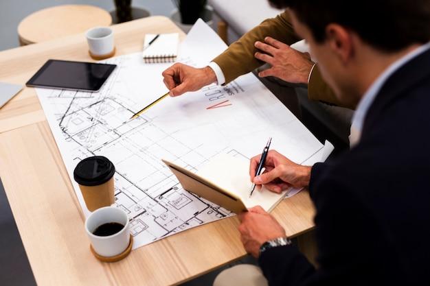 Hoge hoekmedewerkers die samen op kantoor plannen
