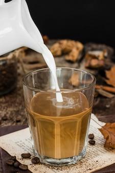 Hoge hoekmelk die in glas met koffie wordt gegoten