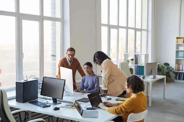 Hoge hoekmening bij divers team van softwareontwikkelaars die computers gebruiken in moderne kantoren, met focus op projectmanagers die toezicht houden op de productie, kopieerruimte