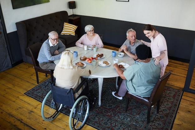 Hoge hoekmening bij diverse groep senioren die genieten van ontbijt aan eettafel in verpleeghuis...