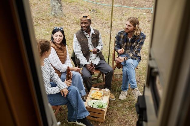 Hoge hoekmening bij diverse groep vrienden die van bier genieten terwijl ze buiten kamperen met een busje