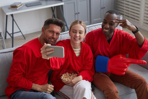 Hoge hoekmening bij een groep sportfans die rood dragen en selfie nemen terwijl ze thuis naar een wedstrijd kijken