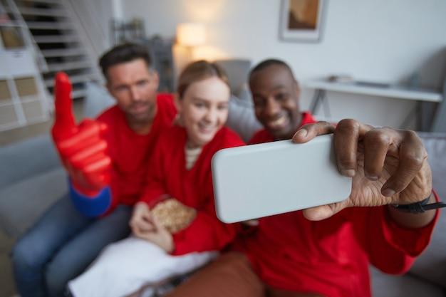 Hoge hoekmening bij een groep sportfans die rood dragen en selfie nemen tijdens het kijken naar een wedstrijd thuis, focus op de voorgrond